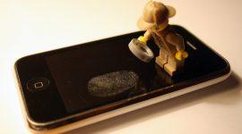 Sherlock Holmes en Lego étudie lune empreinte digitale sur l'écran d'un iPhone.